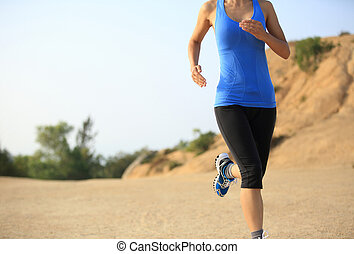young woman runner legs running on seaside mountain trail