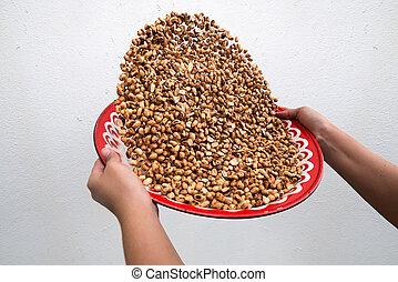 Winnow roasted peanuts on gray wall background - Winnow...