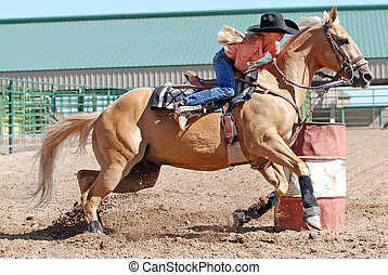 Young blonde barrel racer - Young blonde cowgirl riding a...