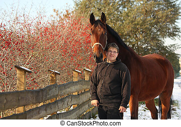 Plump happy teenager boy and brown horse portrait near the...