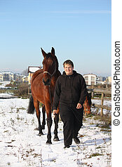 Teenager boy and brown horse walking in the snow in rural...