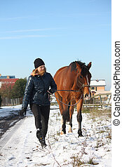 Teenager girl and brown horse walking in the snow in rural...