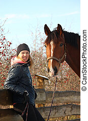 Teenager girl and bay horse hugging each other in fall