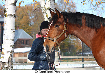 Beautiful teenager girl and bay horse portrait in autumn...