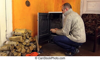 man axe firewood - Villager man in sweater light firewood in...