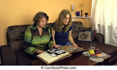 women photo album - Young pregnant woman looking at photo...