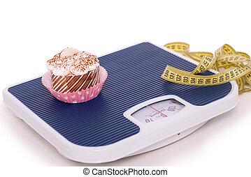 Pastry on weighs with measurer - Concept for obesity issue....