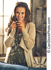 Portrait of smiling young woman with cup of coffee in loft...