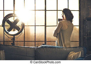 Young woman enjoying cup of coffee in loft apartment rear...