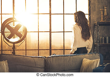 Young woman looking in window in loft apartment rear view