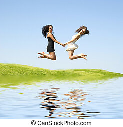 two jumping woman - two happy jumping woman over sky