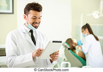 Dentist - Smiling dentist with a tablet in hands. Another...