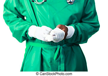 Surgeon putting on his gloves - Senior Surgeon putting on...