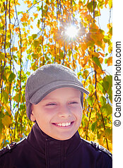 child boy happy smile sun shine autumn leaves backlight