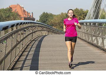 Running girl. Young girl runner on the bridge in European...