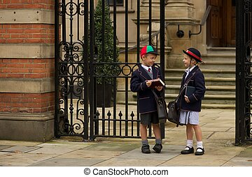 Brother and sister waiting at school gates