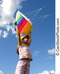 start flying kite - child starts flying kite against blue...