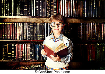 research - Smart boy stands in the library by the...