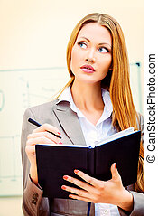 pondering - Portrait of a business woman making notes to her...