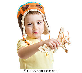 happy kid boy pilot and playing with wooden airplane toy