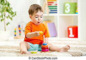 Child boy playing with toy at home