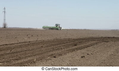 seeder sowing and went away on the black earth's field