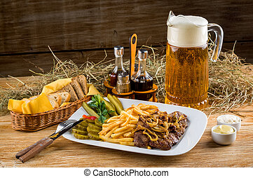 Roast beef, french fries and jug of beer on the rural table