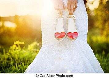 Bride holding wedding shoes - Photograph of a unrecognizable...