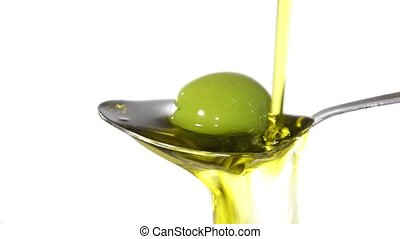 Olive oil on a spoon - Olive oil poured on a spoon over...