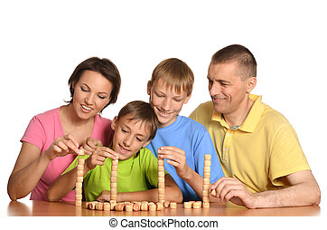 Family of four people playing lotto sitting at table