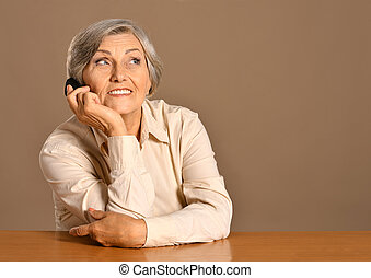elderly woman speaking on mobile against brown background