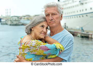 Senior couple standing on pier at the resort during vacation