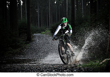 Mountain biker speeding through forest stream Water splash...