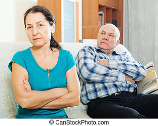 Upset mature woman against husband at home