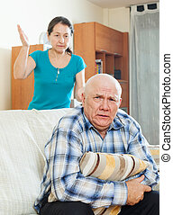 Unhappy senior man with angry wife at home