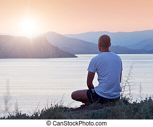 Man looks at the sunset - Man sits on a cliff above the sea...