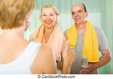 Elderly couple talking to trainer