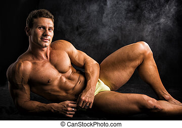 Handsome shirtless muscular man laying down on the floor in...