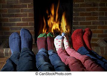 Family Wearing Socks Warming Feet By Fire