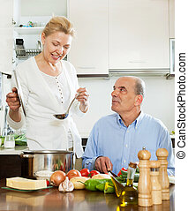 Happy mature woman cooking with husband in kitchen - Happy...