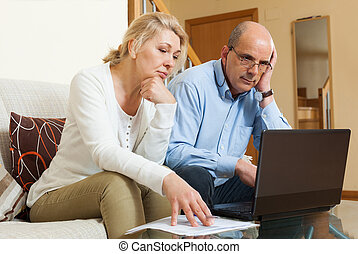 Serious mature couple with laptop at table in home