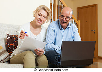 Mature couple with laptop in home - Mature married couple...