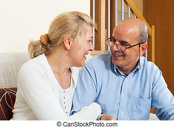 Elderly couple smiling together with happiness in home...