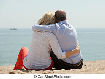 Mature lovers sitting on beach - Romantic mature lovers...