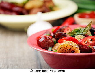 New roasted baked potatoe in the bowl with vegetables