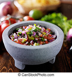 pico de gallo salsa in traditional mexican stone molcajete