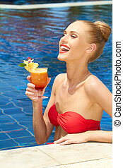 Laughing woman enjoying a tropical cocktail