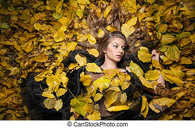 Young woman covered with leaves