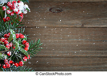 Holly leaves and berries on a wooden background