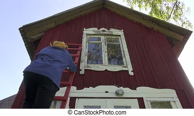 worker in farm scraping old paint from house window